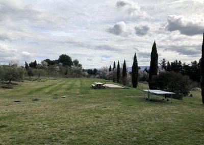 Le grand terrain derrière la piscine avec terrain de pétanque et grande table de pique-nique